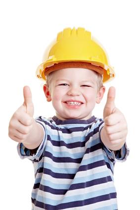 Kind als Bauarbeiter hält Daumen hoch